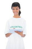 Cheerful black haired volunteer using a tablet pc Stock Photo