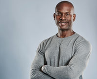 Cheerful black man with folded arms in gray. Single handsome black man with folded arms, cheerful expression and pleasant smile in gray compression shirt over Stock Photos