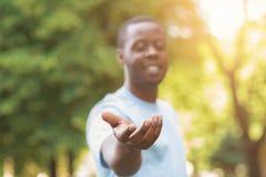 Cheerful black man reach his hand at camera royalty free stock photo