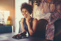 Cheerful black teenage female talking on the phone indoors Royalty Free Stock Photos