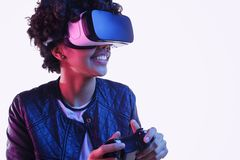 Cheerful black teenager playing VR game stock photography