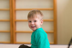 Cheerful blond boy in the gym on a pedestal Stock Images
