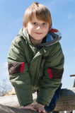 Cheerful blond boy at playground. Playful blond boy climbing at outdoor playground Stock Images