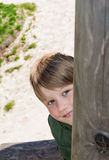 Cheerful blond boy at playground. Playful blond boy peeking around a wooden post at outdoor playground Royalty Free Stock Photo
