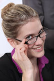 Cheerful blond bussineswoman touching her glasses. Cheerful bussineswoman touching her glasses Royalty Free Stock Photography
