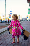 Cheerful blond girl 3 years old with shopping Stock Image