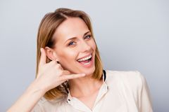 Cheerful blond girl with beaming smile is gesturing to call her. With a hand. She is wearing casual shirt and stands on a light background royalty free stock photography