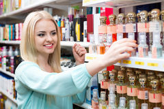 Cheerful blond girl buying perfume in fragrance section. Cheerful beautiful blond girl buying perfume in fragrance section of supermarket Royalty Free Stock Images
