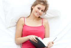 Cheerful blond girl reading a book Royalty Free Stock Photography