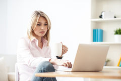 Cheerful blond girl is working on computer Royalty Free Stock Images