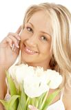 Cheerful blond with white tulips and phone Royalty Free Stock Photo
