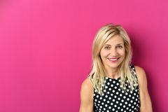 Cheerful Blond Woman Against Pink with Copy Space Royalty Free Stock Photo