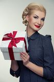 Cheerful blond woman in grey dress with box Stock Photography