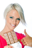 Cheerful blond woman holding a chocolate bar Stock Photography