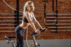 Cheerful blond woman is looking at the camera in the sport center stock photos