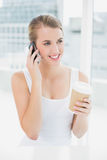 Cheerful blond woman on the phone holding coffee Royalty Free Stock Photos