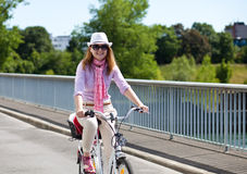 Cheerful Blond Woman Riding A Bicycle Royalty Free Stock Images