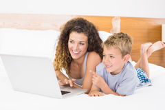 Cheerful blonde boy and mother lying on bed using laptop Royalty Free Stock Photos