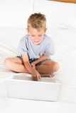 Cheerful blonde boy sitting on bed using laptop Stock Photography