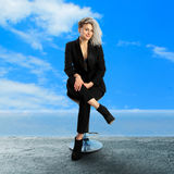 Cheerful blonde business woman sits on chair Royalty Free Stock Photos