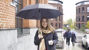Cheerful blonde businesswoman with a coffee and umbrella in a street. Cheerful blonde businesswoman wearing a coat and a scarf is standing with a coffee under an stock footage
