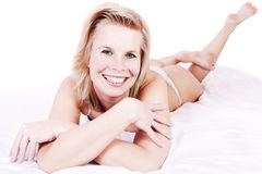 Beautiful blonde girl in bed smiling cheerfully. Royalty Free Stock Photography
