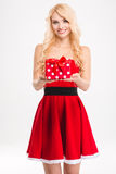 Cheerful blonde girl in red santa claus costume holding present Royalty Free Stock Photography