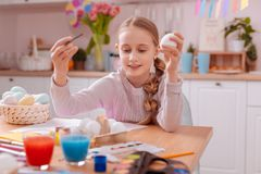 Cheerful blonde girl taking clean egg from holder. Creative childhood. Beautiful little female expressing positivity while turning on her creativity stock photography