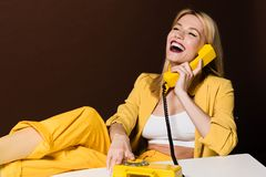 cheerful blonde girl talking by yellow vintage phone and laughing royalty free stock image