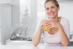 Cheerful blonde having orange juice Stock Image