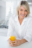 Cheerful blonde having orange juice in kitchen Royalty Free Stock Photo