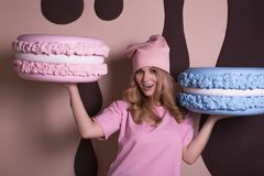 Cheerful blonde model in pink t shirt and cap holding big tasty royalty free stock image