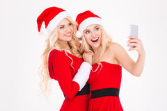 Cheerful blonde sisters twins making selfie using cell phone Royalty Free Stock Photography