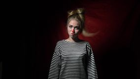 Cheerful blonde in a striped shirt and a clown makeup, slow motion stock footage
