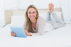 Cheerful blonde using tablet pc on the bed Stock Photos