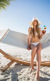 Cheerful blonde wearing bikini and sunhat sitting on hammock wit Royalty Free Stock Images