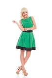 Cheerful blonde woman in green dress Stock Image