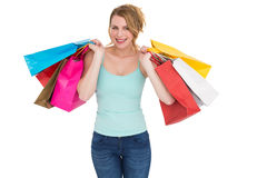 Cheerful blonde woman holding shopping bags. On white background Stock Photo