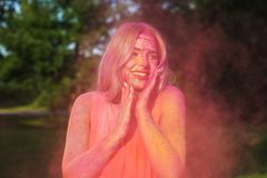 Cheerful blonde woman with long hair covered pink dry paint celebrating Holi festival. Cheerful blonde girl with long hair covered pink dry paint celebrating stock image