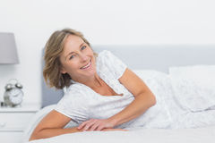 Cheerful blonde woman lying on bed Stock Photo