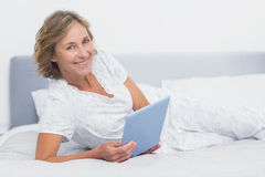 Cheerful blonde woman lying on bed using tablet pc Stock Photos