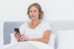 Cheerful blonde woman sending text message in bed Royalty Free Stock Image