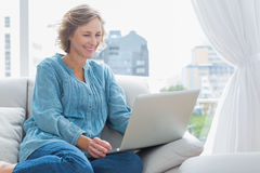 Cheerful blonde woman sitting on her couch using laptop Royalty Free Stock Photography