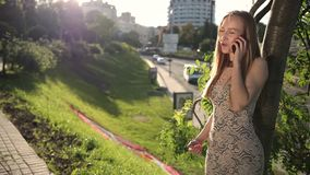 Cheerful blonde woman talking on phone outdoors stock video