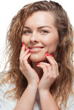 Cheerful blonde woman touching her face and smiling at camera royalty free stock photo