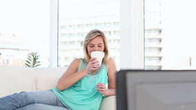 Cheerful blonde woman watching the television stock video footage