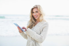 Cheerful blonde woman in wool cardigan using a tablet pc Royalty Free Stock Photography