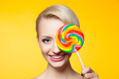 Cheerful blondie with lollipop covering eye Royalty Free Stock Image