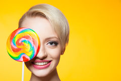 Cheerful blondie with lollipop covering eye Stock Images