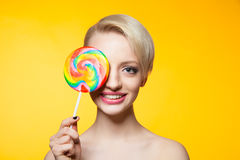 Cheerful blondie with lollipop covering eye Stock Image